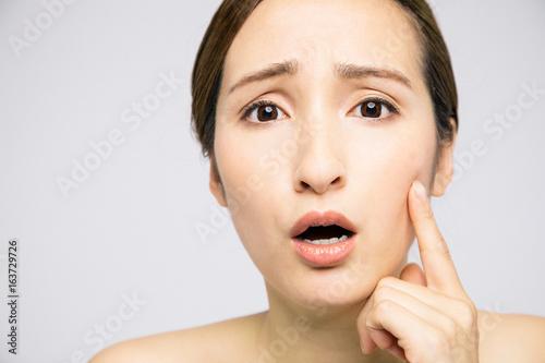 Fotografie, Obraz  beauty woman who checks her skin, skin care, acne treatment
