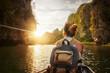 Leinwandbild Motiv Woman traveling by boat enjoying sunset among of karst mountains