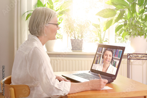 Telecounseling concept, senior woman at home in front of a laptop making notes during an online video call with a female therapist