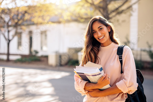 Fotografie, Tablou Female college student with books outdoors