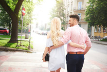 Rear View Of Couple Walking In Street Arms Around Each Other