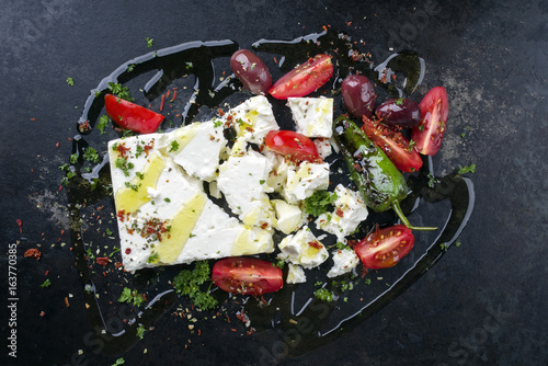 Fototapeta Traditional Greek feta with vegetable as top view on an old rusty bord obraz