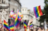 Fototapeta Rainbow - A spectator waves a gay rainbow flag at an LGBT gay pride march in London