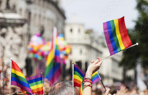 A spectator waves a gay rainbow flag at an LGBT gay pride march in London Canvas Print