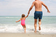 Father and daughter running in the sea.