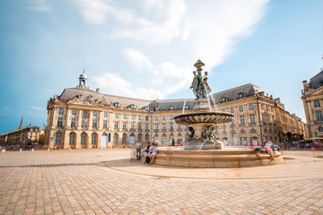 View on the famous La Bourse square with fountain in Bordeaux city, France. Long exposure image technic with motion blurred people and clouds