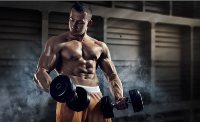 Fototapeta na wymiar Sport and fitness. Muscular bodybuilder in the gym training with dumbbells