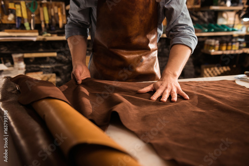 Obraz Close up of a cobbler working with leather textile - fototapety do salonu