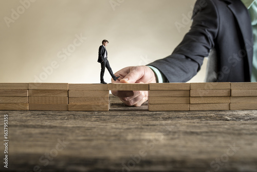 Fotografía  Building bridge to span a gap for little businessman