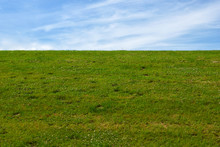 Dike With Green Meadow And Blue Sky