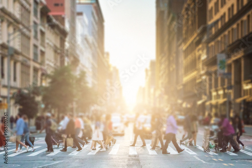 Anonymous group of people walking across a pedestrian crosswalk on a New York City street with a glowing sunset light shining in the background - 163809761