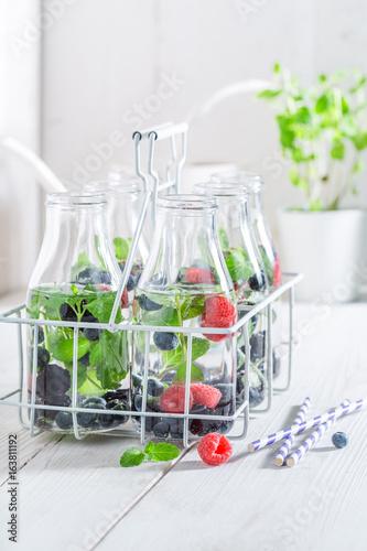 Staande foto Vlees Fresh water in bottle with berries on white table