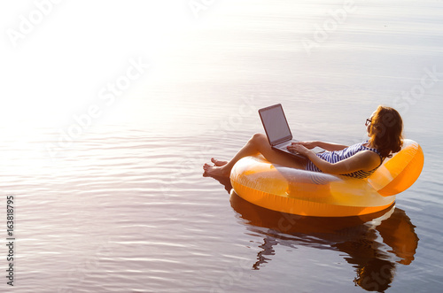 Fotografía  Business woman working on a laptop in an inflatable ring in the water, a copy of the free space
