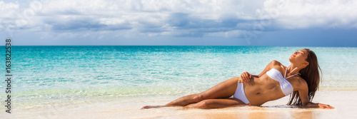 Sexy fashion bikini woman sunbathing lying down banner. Panorama landscape crop of white sand beach Asian model relaxing with slim figure on tropical travel summer holidays.