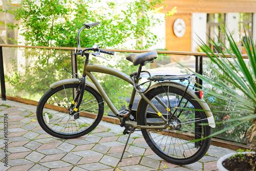 Fotobehang Fiets Vintage khaki bike in the sunrise in the courtyard