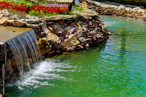Foto op Plexiglas Indonesië Amazing waterfall azure lake with crystal clear water among green woods