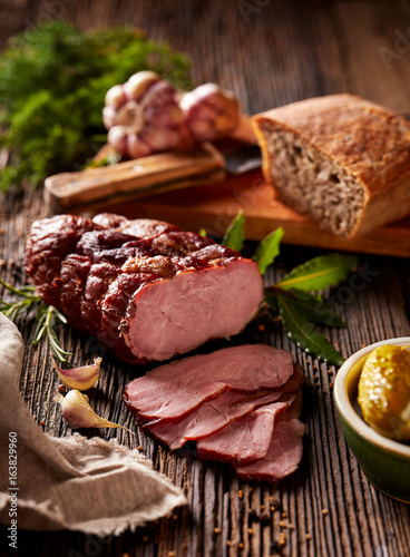 Sliced smoked ham  on a wooden  table with addition of fresh  herbs and aromatic spices.   Natural product from organic farm, produced by traditional methods