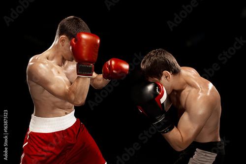 Plakat Dwa profesjonalne bokserskie boksowanie na czarnym tle,