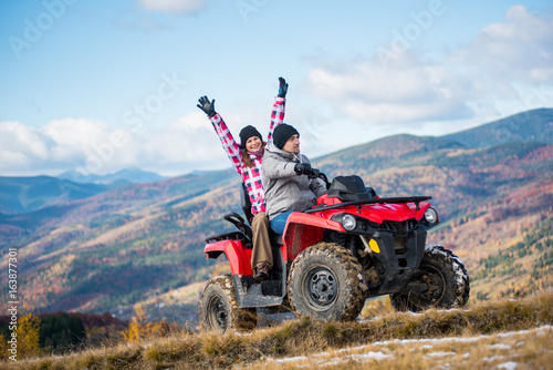 Guy drive atv quad bike, girl sitting behind him and raised her hands up on a mountain road on a background of beautiful landscape mountains and blue sky