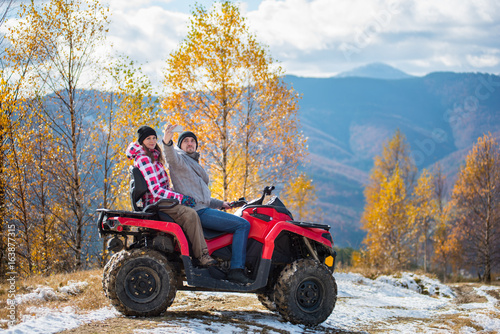 Man with woman in winter clothing on red quad bike makes selfie on the phone against blurred background of autumn landscape