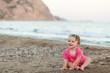 Cute little girl sitting on a beach