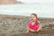 Cute little girl sitting on a beach
