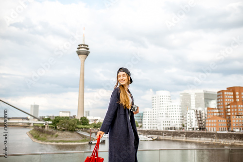 Fotografia Young woman tourist standing with photo camera with famous television tower and