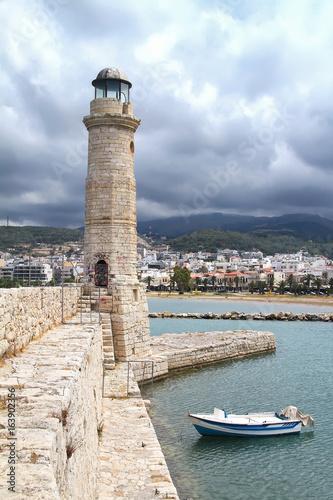 Deurstickers Canarische Eilanden Stone pier, lighthouse and boat in the port of Chania. Crete