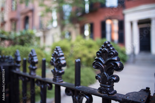 Beautiful wrought iron fence with carved posts in an old colonial neighborhood in New England Canvas Print