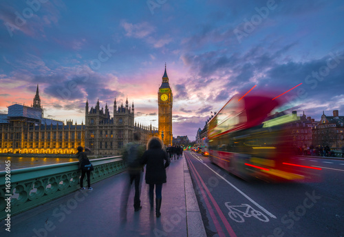 Photo London, England - Iconic Red Double Decker Bus on the move on Westminster Bridge with Big Ben and Houses of Parliament at background