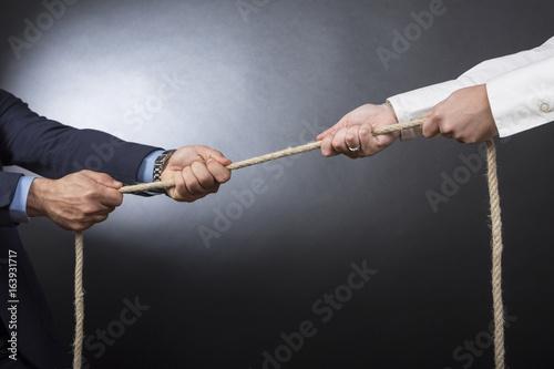 Fotografie, Obraz  Dettaglio due mani che tirano una fune  in segno di sfida - sfondo nero e bianco