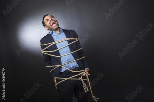 Uomo con giacca e camicia legato da un fune urla disperato perché non può muover Slika na platnu