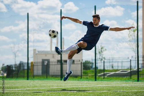 Fototapeta athletic soccer player kicking ball on soccer pitch
