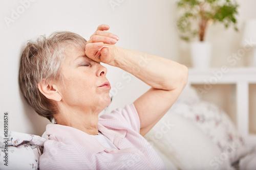 Fotografia  Seniorin mit Kopfschmerzen liegt im Bett