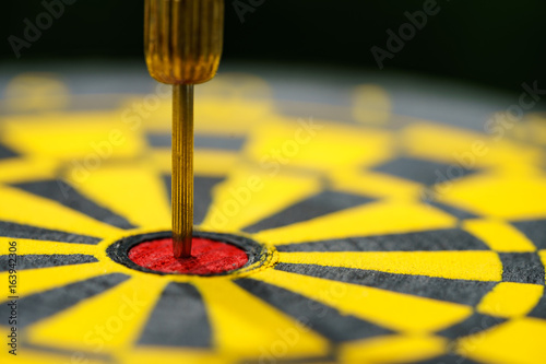 Fotografía  Selective focus on gold needle dart in the center of dartboard as Business goal