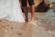 Groom`s and bride`s feet on the beach
