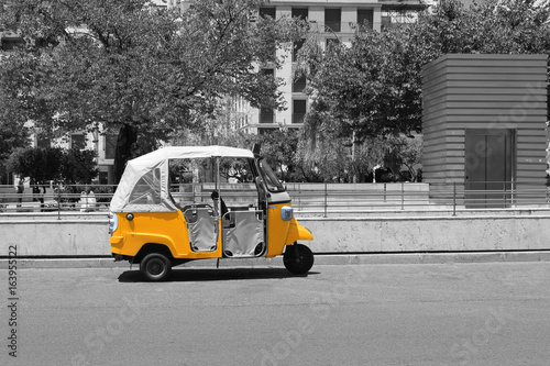 black-and-white-picture-of-tuk-tuk-small-passenger-three-weel-mini-car-isolated-on-summer-empty-street-road-background-bright-yellow-rickshaw-helps-tourists-to-travel-around-the-city-fast