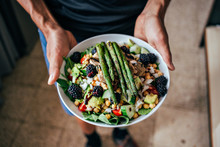Man Hands Holding Big Deep Plate Full Of Healthy Paleo Vegetarian Salad Made From Fresh Organic Biological Ingridients, Vegetables And Fruits, Berries And Other Nutritional Things