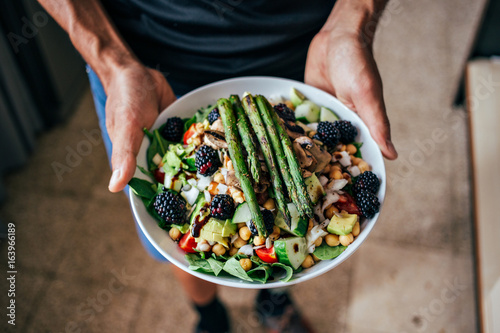 Obraz Man hands holding big deep plate full of healthy paleo vegetarian salad made from fresh organic biological ingridients, vegetables and fruits, berries and other nutritional things - fototapety do salonu