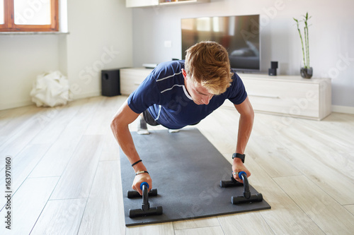 Ragazzo fitness a casa  pettorali con manubri Canvas Print