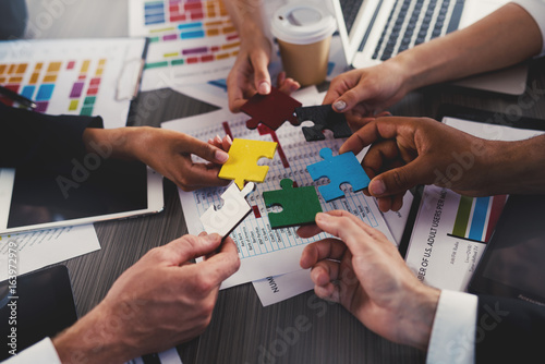 Fototapety, obrazy: Businessmen building colored puzzles together. Concept of teamwork, partnership, integration and startup