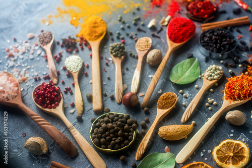 Spoed Foto op Canvas Chocolade Various indian spices in wooden and silver spoons and metal bowls, seeds, herbs and nuts on dark stone table. Colorful spices, selective focus. Organic food, healthy lifestyle.