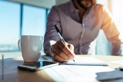 Photo  Businessman making notes at his desk.