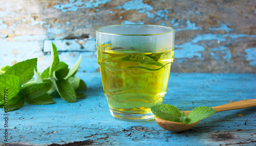 Photo  glass of herbal Melissa mint tea on a wooden table