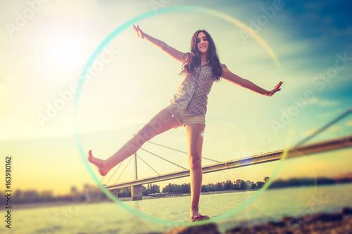 Obraz na plátně  Teenage girl balancing on the stone while the sun sets / Cheerful teenage girl b