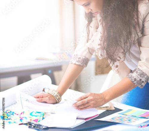 Fototapety, obrazy: Smiling female fashion designer sitting at office desk