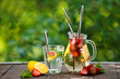 Refreshing sweet homemade strawberry lemonade in jug on wooden table
