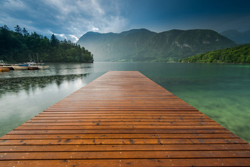 Fototapeta Molo Tranquil and symetric wooden pier at Lake Bohijn, Slovenia