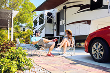 Young Couple Sits Near Camping Trailer,smiling.Woman And Men Drinking Water, Relaxing On Chairs Near Car And Palms.Family Spending Time Together On Vacation Near Sea Or Ocean In Modern Rv Park