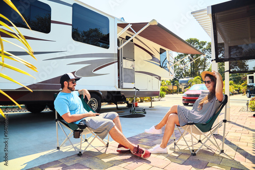 Foto op Canvas Kamperen Young couple sits on chairs near camping trailer and car